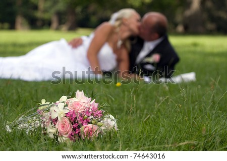 Young marrieds behind a wedding bouquet - stock photo