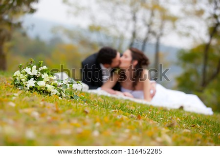 Young marrieds kissing behind a wedding bouquet - stock photo