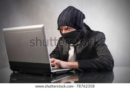 Young masked hacker using a laptop