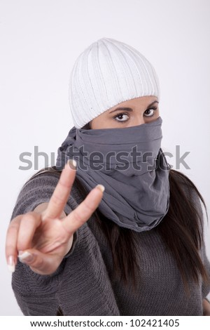 Young masked woman with showing peace sign with her fingers