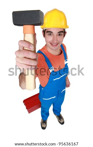 Young mason displaying lump hammer - stock photo