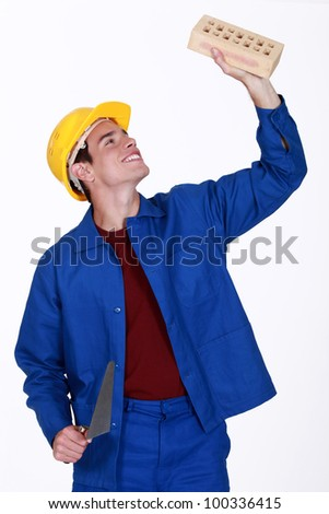 Young mason holding brick and trowel - stock photo