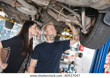 Young mechanic and woman looking at machine of car in auto repair shop - stock photo