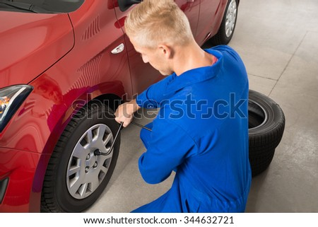 Young Mechanic Changing Tire In Garage With Wrench - stock photo