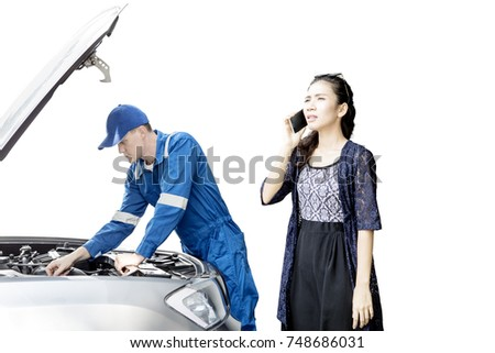 Young mechanic checking broken car while standing with his stressed customer, isolated on white background