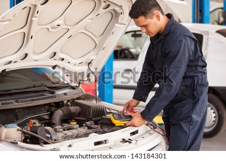 Young mechanic checking the voltage of a battery using a voltmeter - stock photo