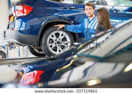 Young mechanic discussing with female customer while standing by car in garage - stock photo