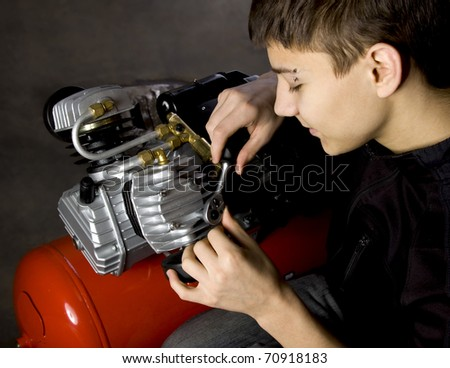 Young mechanic fix engine - stock photo