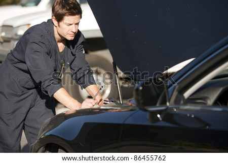 Young mechanic fixing a car - stock photo