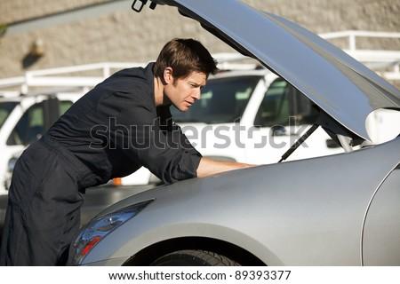 Young mechanic fixing a car - stock photo