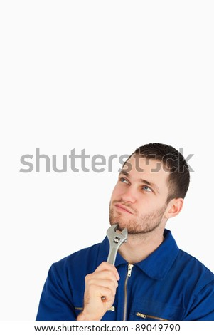 Young mechanic in boiler suit in thoughts against a white background - stock photo
