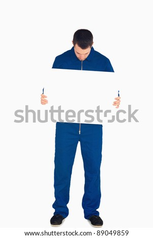 Young mechanic in boiler suit looking on banner in his hands against a white background - stock photo