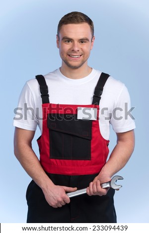 Young mechanic in red and black overall standing against blue background. smiling man holding spanner and looking into camera - stock photo
