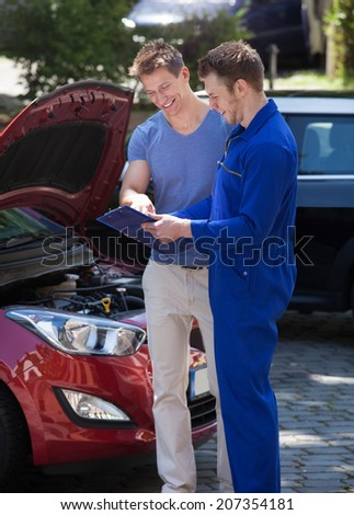 Young mechanic showing clipboard to customer by breakdown car - stock photo