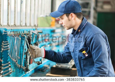 Young mechanic taking some tools in his shop - stock photo
