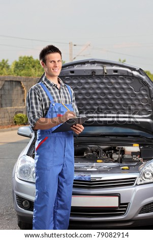 Young mechanic with a clipboard standing next to a car with open hood - stock photo