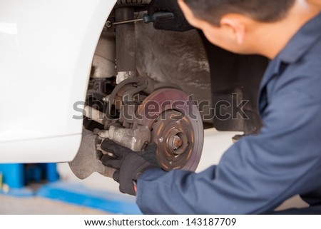 Young mechanic working on a car and fixing its suspension at an auto shop - stock photo