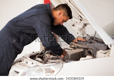 Young mechanic working on a car engine at an auto shop - stock photo