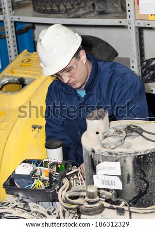 Young mechanic working on production equipment. - stock photo