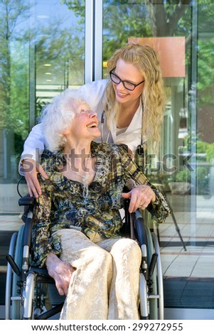 Young Medical Assistant and her Elderly Woman Patient on a Wheelchair Laughing Together Outside the Nursing Home. - stock photo