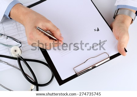 young medical doctor prescribing something/ Cardiogram of the heart and phonendoscope behind - stock photo