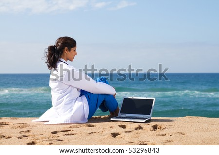 young medical doctor with laptop on beach - stock photo