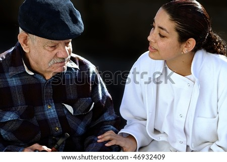 young medical personel helping an old man - stock photo