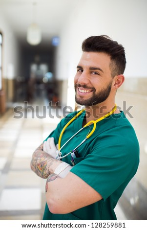 Young medical worker with tatoos on his arms - stock photo