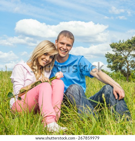 Young men against nature - a green meadow and dark blue sky with clouds - stock photo
