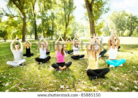 young men and women doing yoga outdoor - stock photo