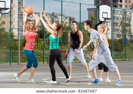 Young men and women playing basketball in a park - stock photo