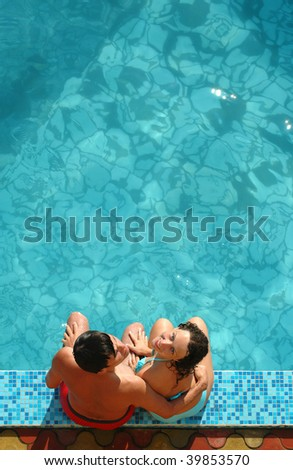 Young men and women sits beside water pool - stock photo