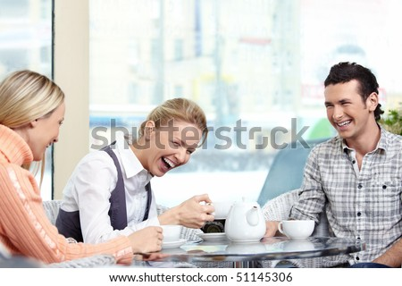 Young men behind a table in the foreground laugh - stock photo