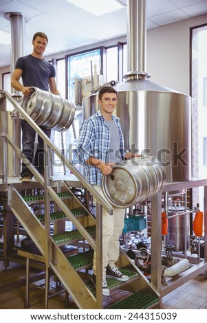 Young men carrying keg smiling at camera in the factory - stock photo