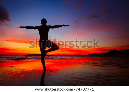 Young men doing exercises on wet sand - stock photo