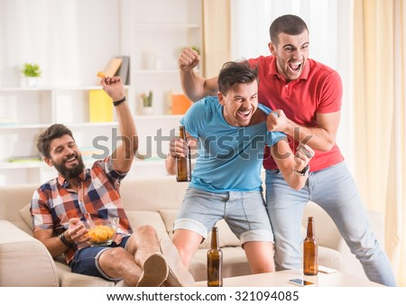 Young men drink beer, eat pizza and cheering for football - stock photo