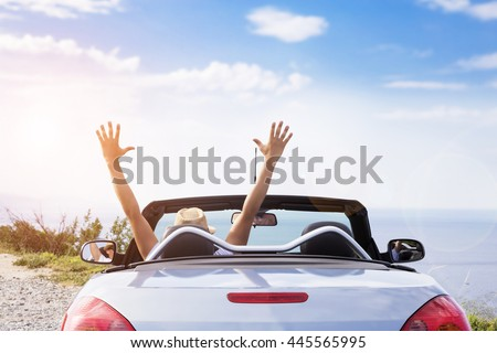 Young men drive a car on the beach. - stock photo