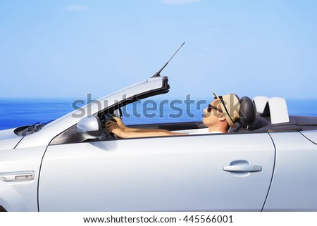 Young men drive a car on the beach - stock photo