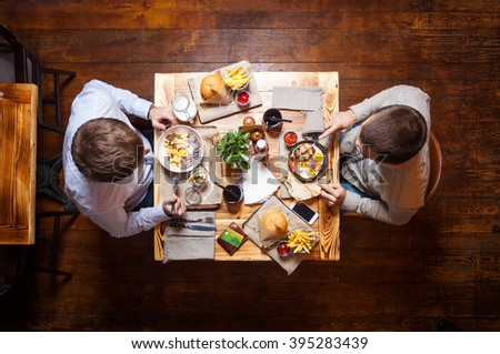 Young men eating out in cafe or restaurant - stock photo