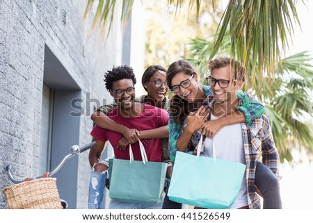Young men giving piggyback to women having fun - stock photo