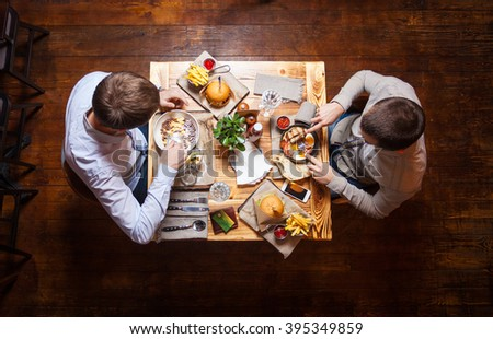 Young men having lunch at a cafe, view from above - stock photo