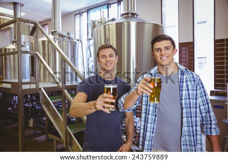 Young men holding a pint of beer smiling at camera in the factory - stock photo