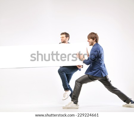 Young men holding empty board - stock photo