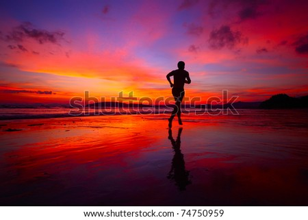 Young men jogging on wet sand by sea edge on vivid sunset background - stock photo