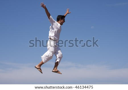 young men jumping and raising his arms up to the air - stock photo