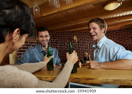 Young men laughing at woman drinking beer in pub.? - stock photo