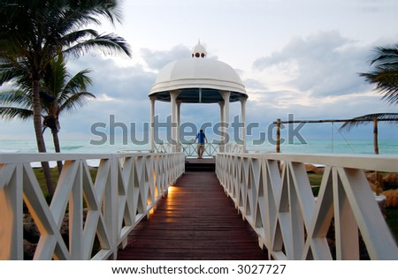 young men looking at the ocean inside of a small chapel, conceptual dream - stock photo