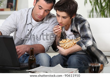 Young men looking with interest at a laptop - stock photo
