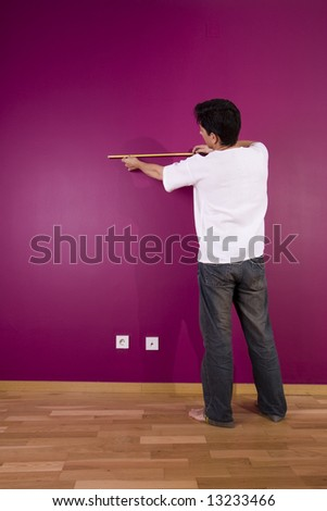 young men measuring to redecorate a new painted wall - stock photo