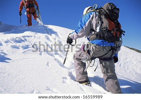 Young men mountain climbing on snowy peak - stock photo